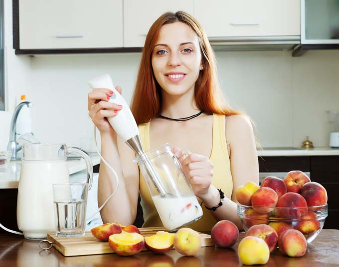 Attractive woman with immersion blender inserted into cotnainer behind kitchen coutner with fruts and vegetables scattered about on coutnter. Othe accessories also on counter.