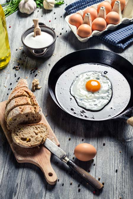 fried egg in skillet with bread, cream, and a carton of eggs nearby