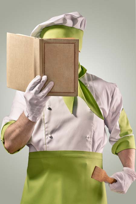 A cook studying food related terms and definitions from a book.