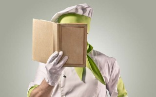 A cook examines a book containing cooking terms, lingo, and definitions.