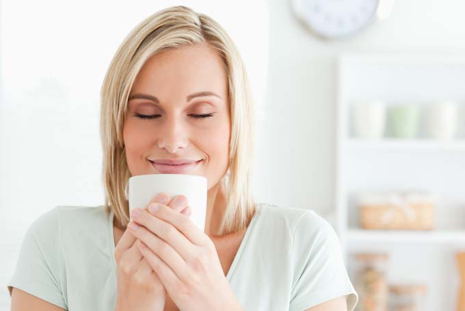 Pretty blonde healthy looking woman savors a cup of coffee by smelling it; has a satifised smile on her face