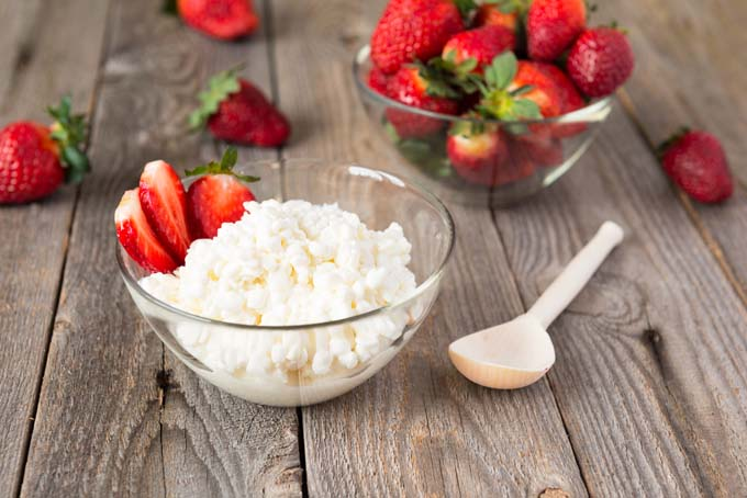 Homemade Cottage Cheese And Strawberries On Rustic Wooden Table. Cottage In  Front And Bowl Of