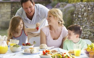 arrtactive couple with son and daughter in an outside brunch consiting of healty foods; daughter is holding strawberry in the air and parents are laughing