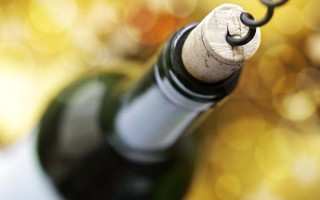 A corkscrew enters the cork in the top of a bottle of wind; defocused background