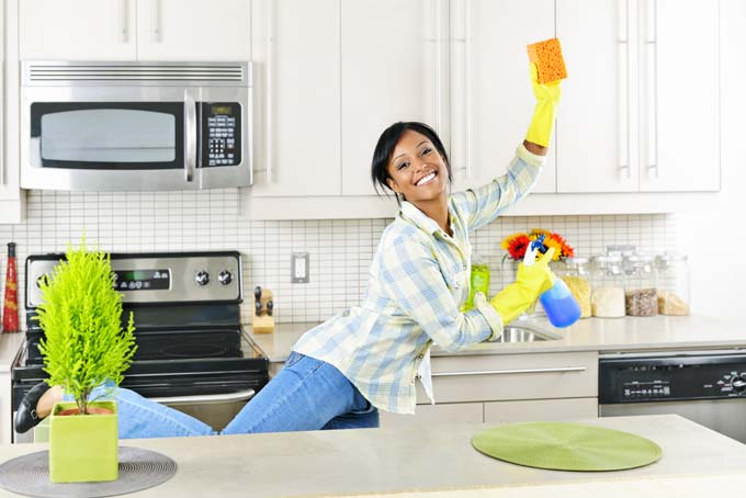 Attractive young femaing dancing in the Kitchen to exercise and burn off calories