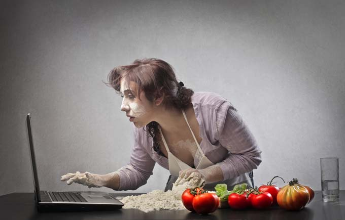 attractive young female looks at food recipes and pictures on her laptop as she tries to prepare a meal. Ingredients are spread all over counter and she had flour stock to her fingers.