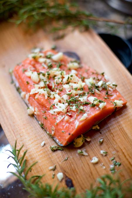 Pln with salmon with onions, herbs, and spices placed on top. Plank is setting on grill.