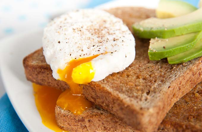 poached egg on toast with yolk running down bread and onto the plate; cuccumber slices on the side