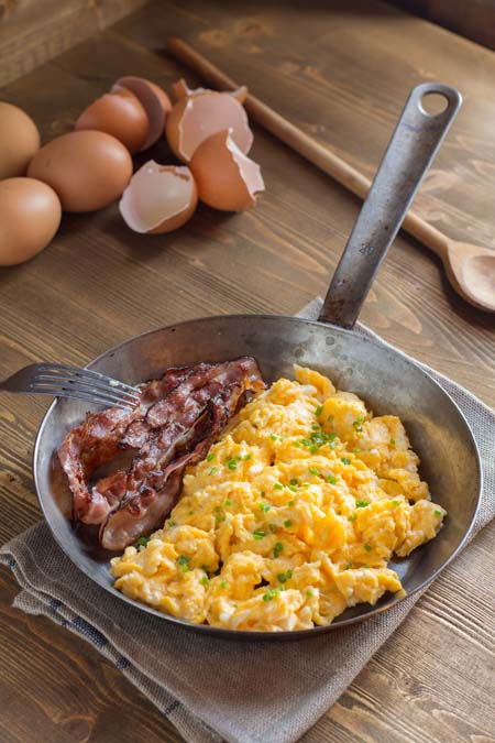 scrambled eggs with bacon in steel pan on wooden table with broken shells in the bacground