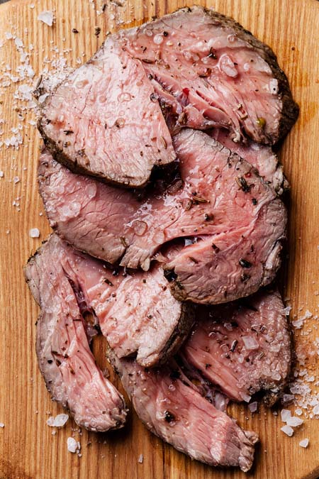 slow cooked roast beef sliced on wooden cutting board