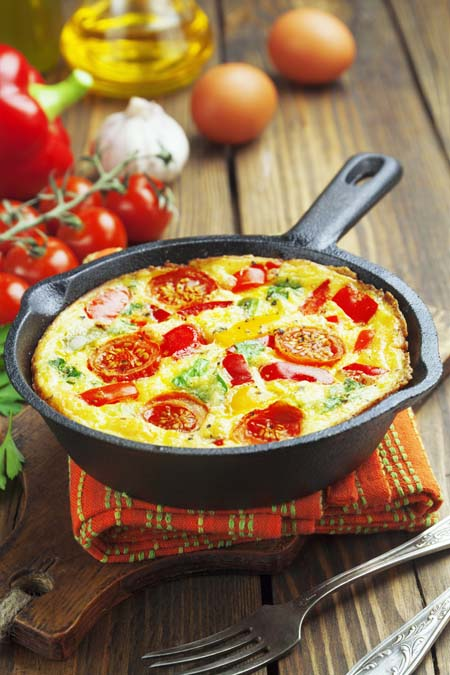 tomato and vegetable frittata in cast iron frying pan