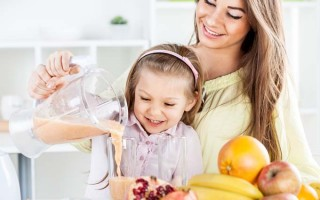 Mother and daughter pour a smoothie from a blender; they are behind a kitchen counter that includes oranges, kiwi,bananas and other fruit on its surface