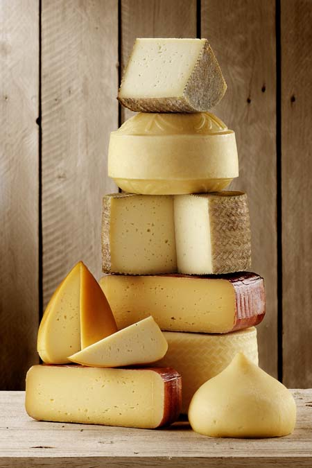 Different types of cheese stacked up on a counter; rustic wooden wall in background.