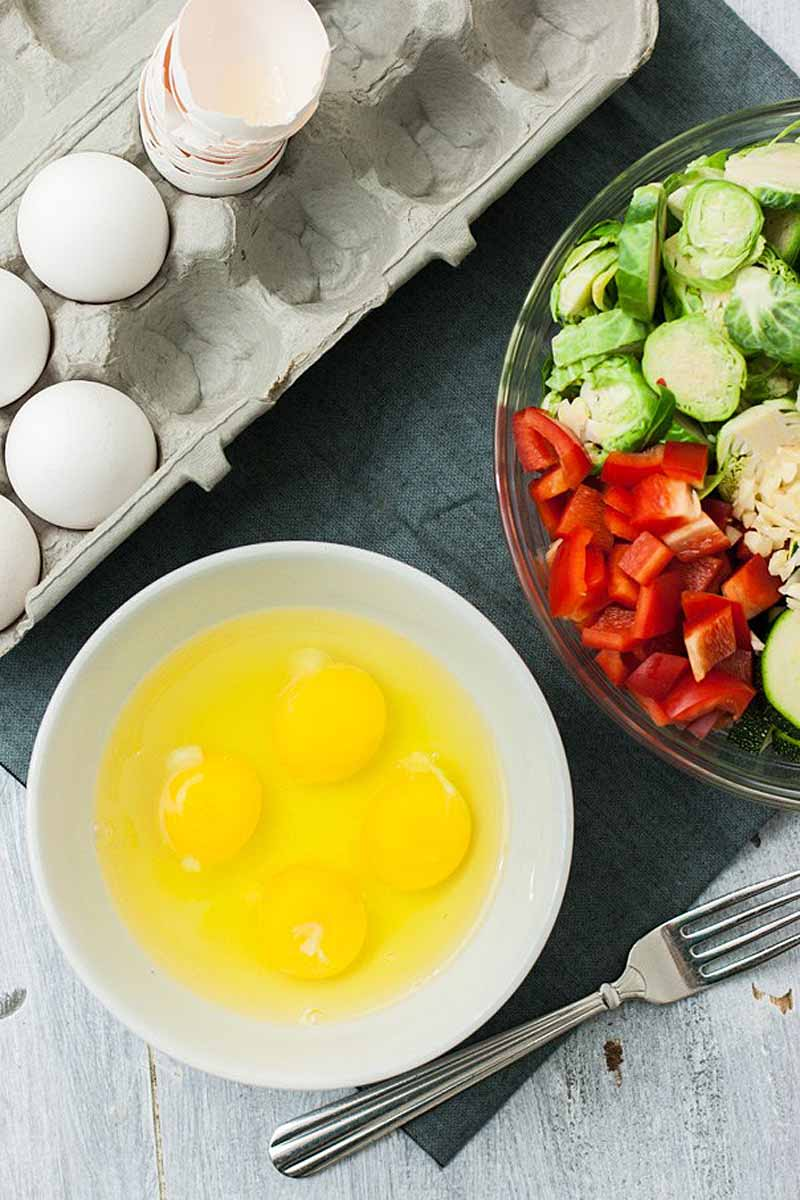 Top down view of four eggs cracked into a white, ceramic bowl. The remainder of the carton is at the top of the photo with the bowl of sliced veggies to the right.