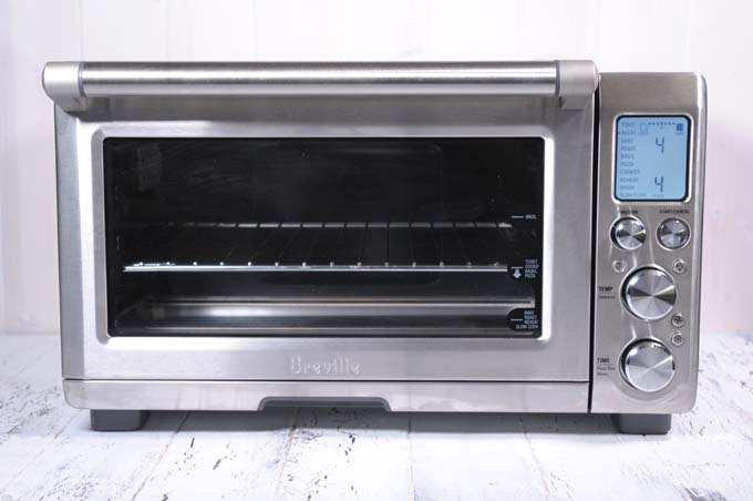 Breville Smart Oven Air sitting on a white painted wooden surface