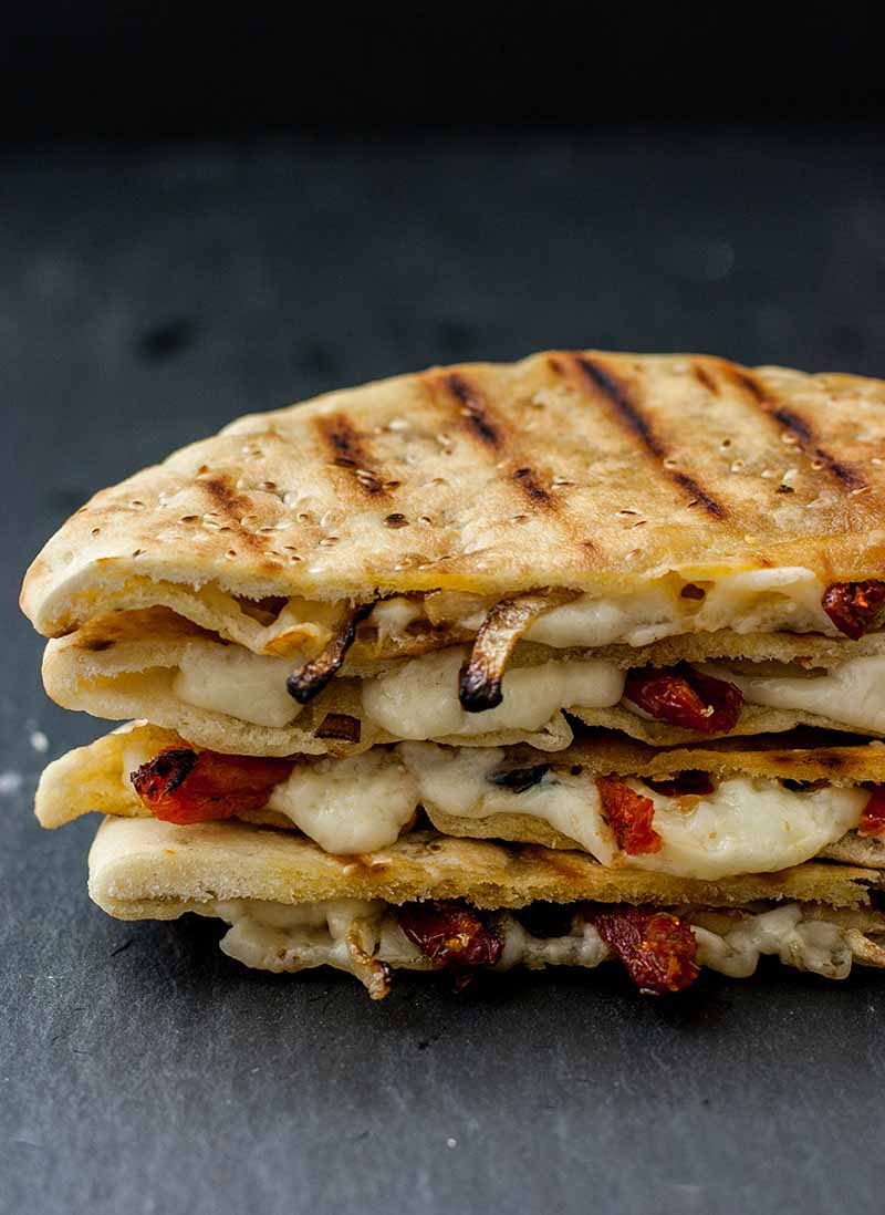 Close up of a a half of a sandwhich made with white cheddar cheese, pita bread, caramelized onions, and sundried tomatoes on a black stone surface