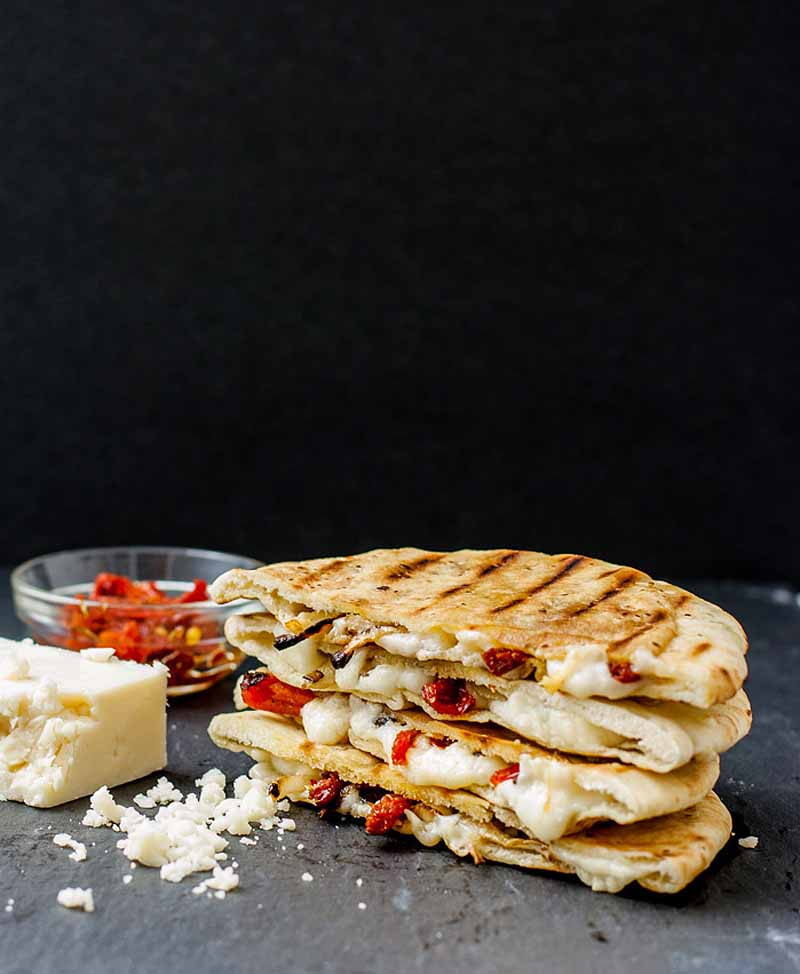 A caramelized onion and sundried tomato grilled cheese pita on a solid black background. A block of white cheddar cheese and a small glass bowl full of extra sundried tomatoes sit next to the sandwich.