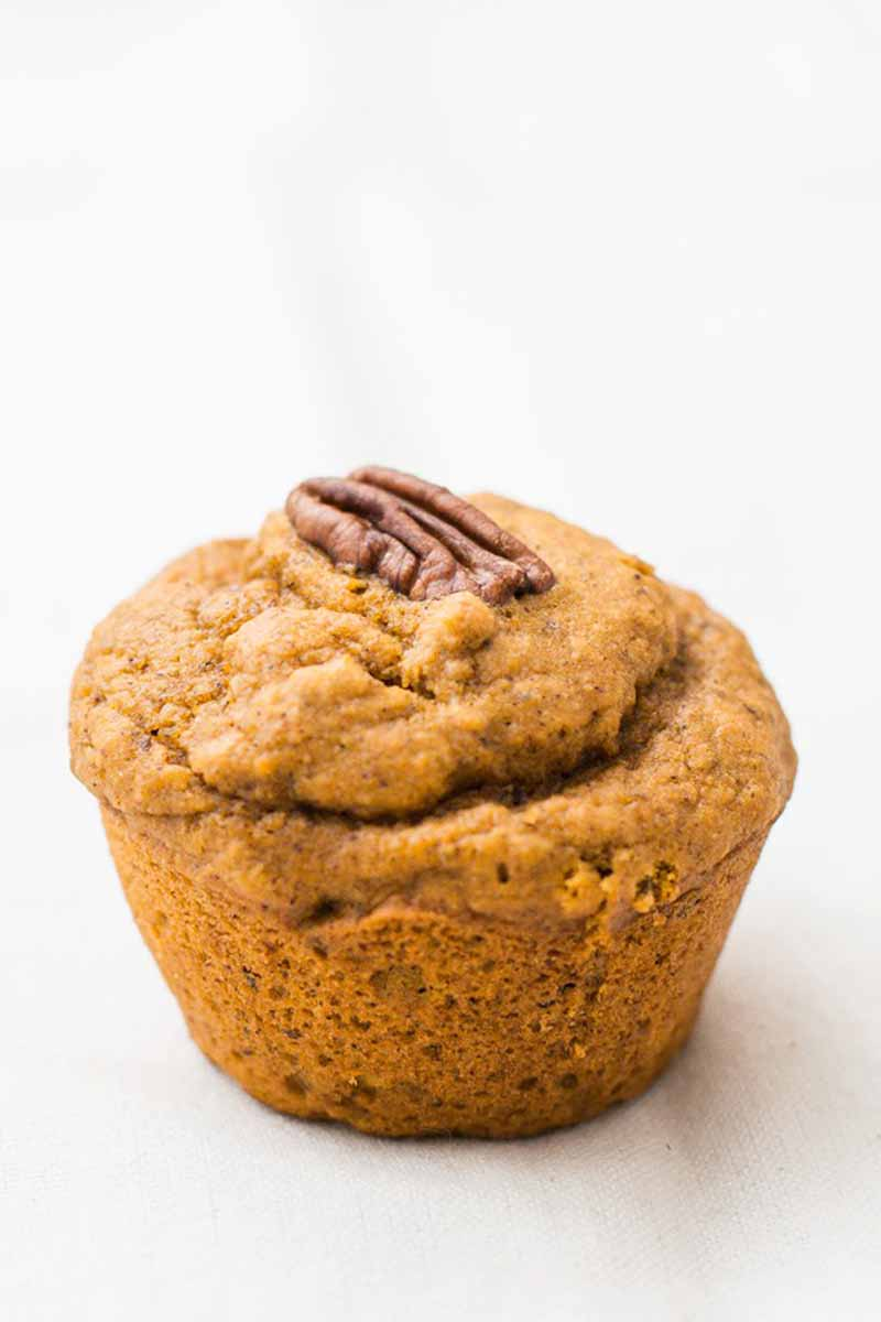 Vertical image of one orange muffin with a pecan garnish.