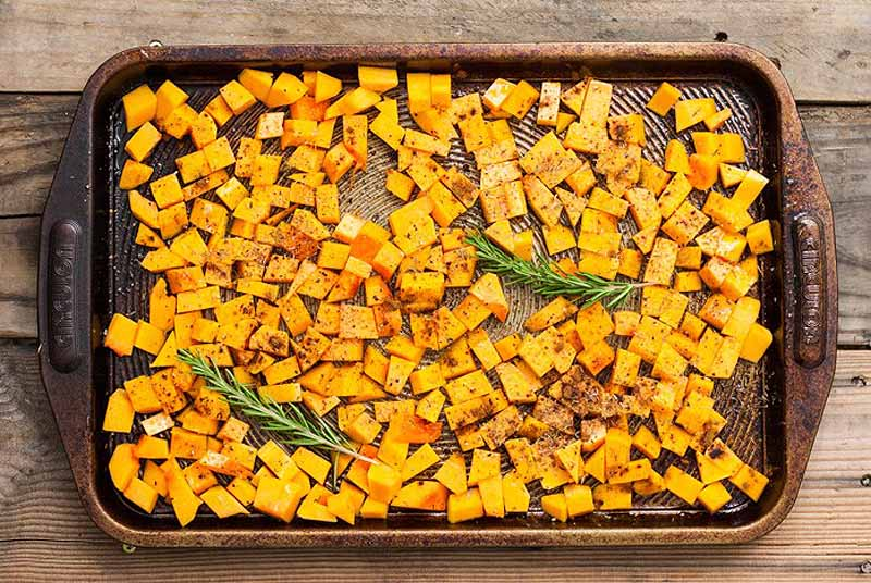 Top down view of roasted cubed butternut squash on a baking sheet.