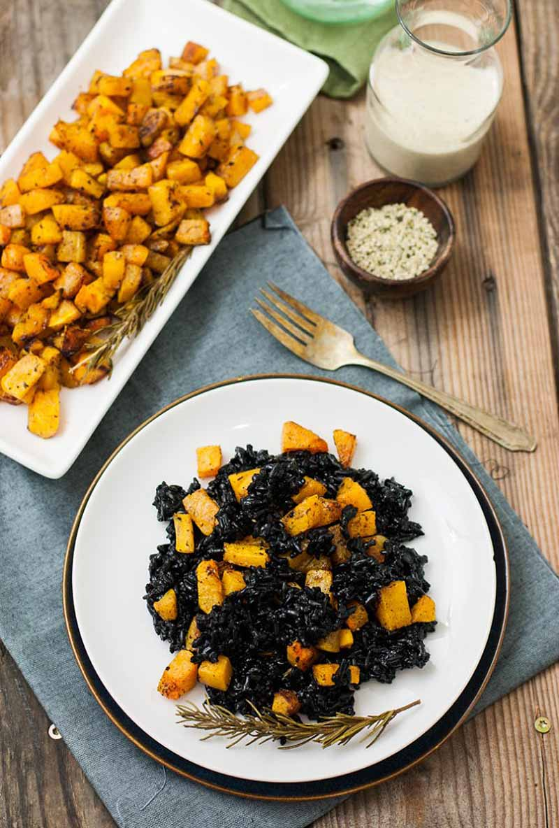 Top down view of a white ceramic plate full of roasted butternut squash and black rice with a dressing made of miso and hemp seeds. A rectangular platter for of more cubed roasted squash sits and the top of the image.