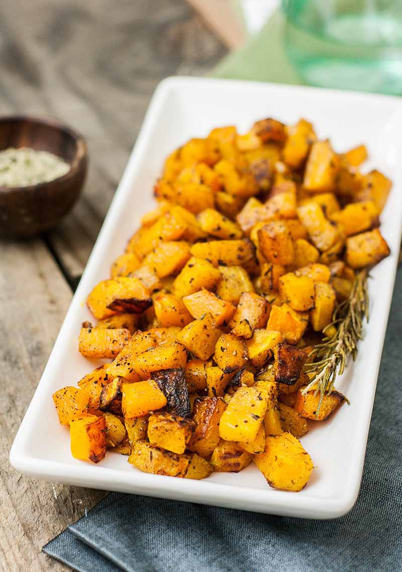 A square white platter fulled of cubed and roasted butternut squash.