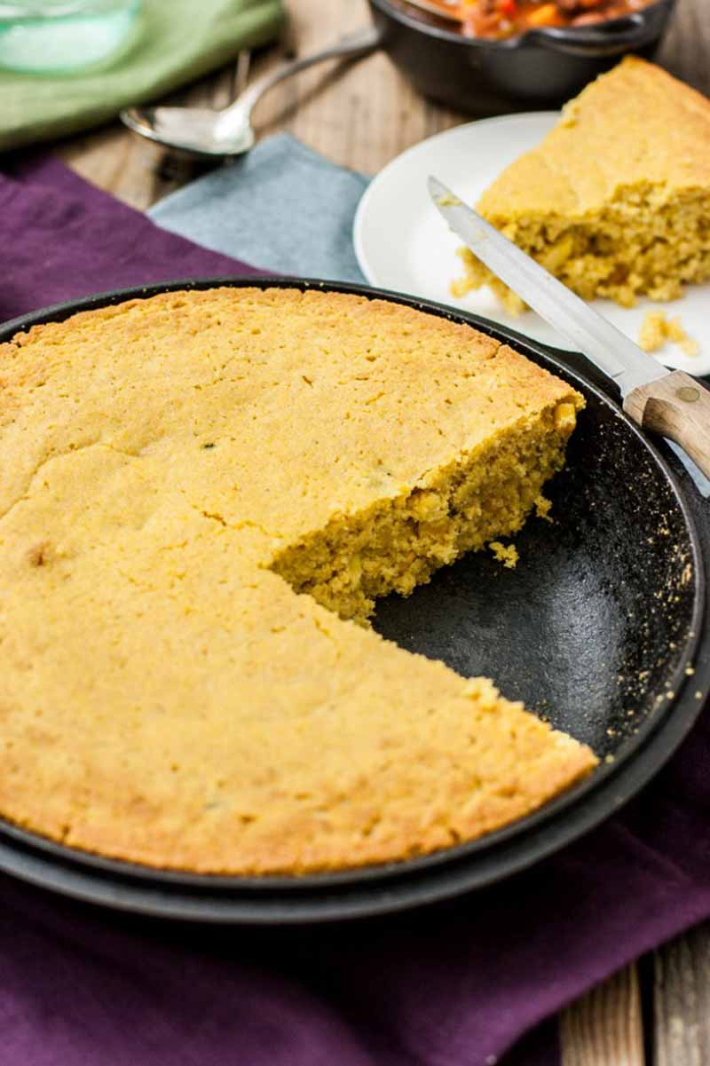 An oblique view of a cast iron pan full of vegan roasted jalapeno cornbread in a cast iron pan. One slice has been removed.