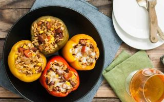 Top view of four vegetarian southwest style stuffed bell peppers inside of a ceramic slow cooker. Two are prepared vegan-style and are dairy free and two have melted pepper-jack cheese on top.