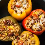 Close up top view of four stuffed southwest style bell peppers in crock-pot. Two are dairy-free and two have cheese.