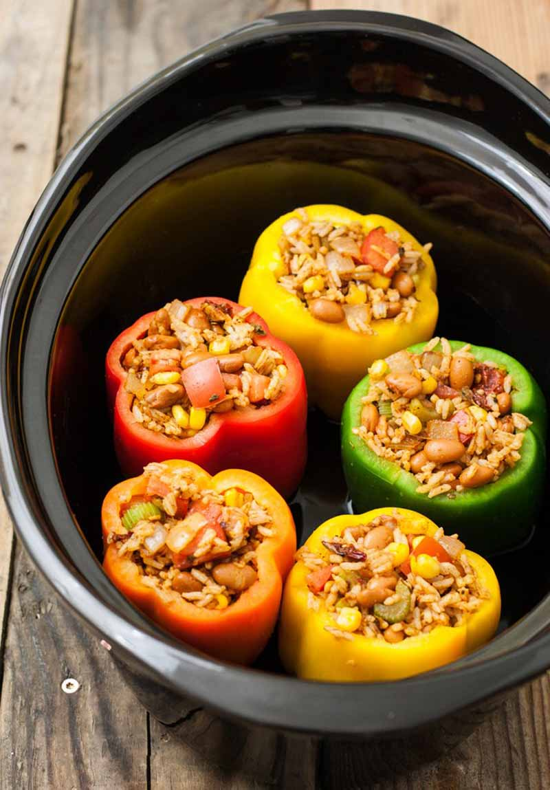 Top-down shot of a slow cooker metal insert with five vegetarian stuffed peppers in various colors at the bottom, on an unfinished wood background.