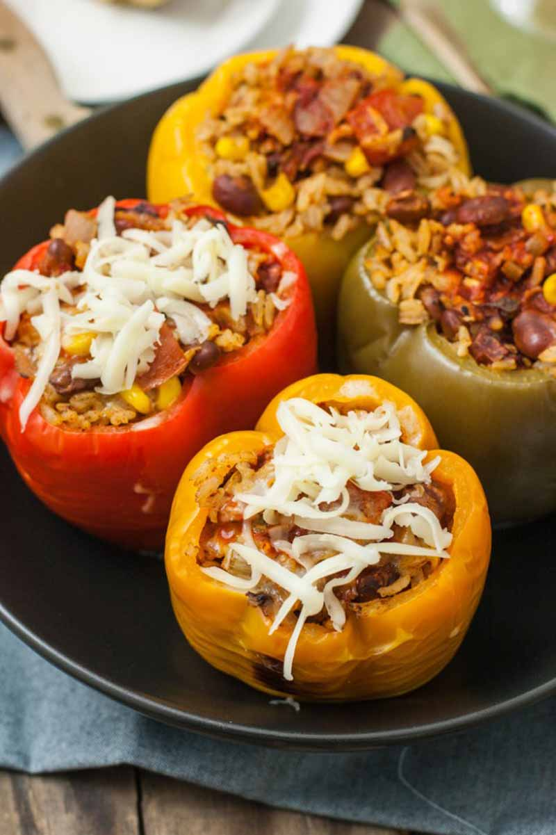 Oblique top-down view of meatless southwest style stuffed bell peppers made in a slow cooker. The focus is on two peppers that have cheese sprinkled on top.
