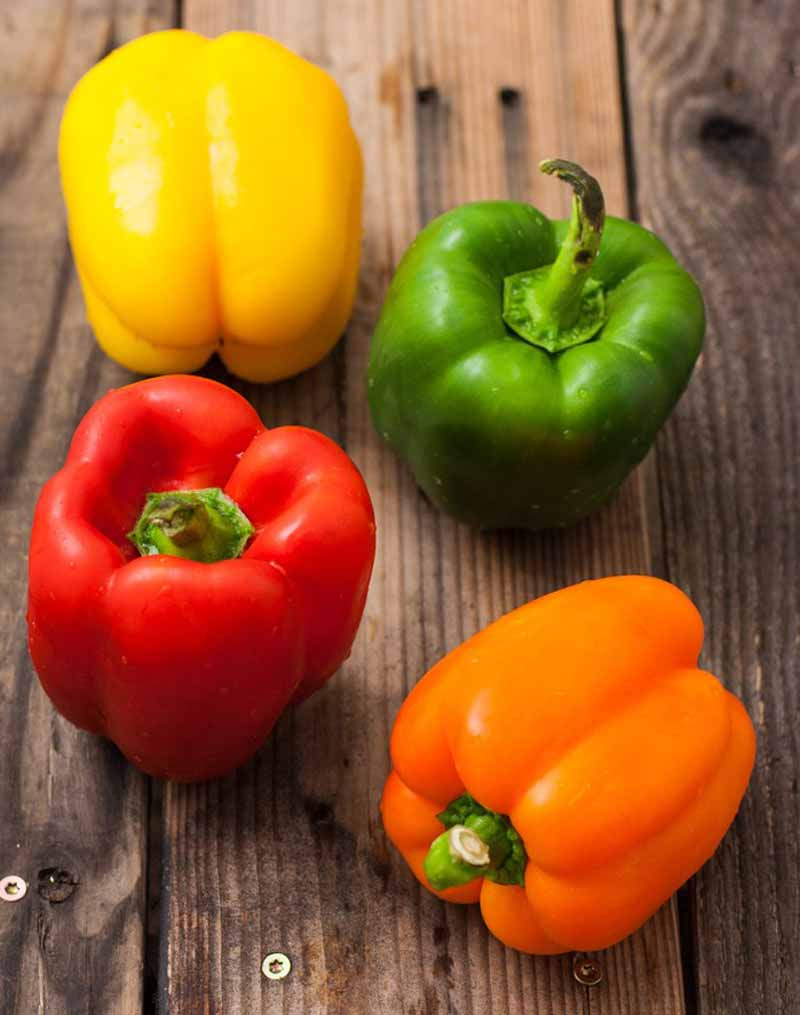 Fresh orange, green, red, and yellow bell peppers on a rustic wooden surface.