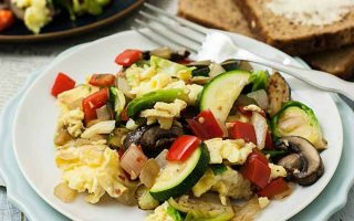 A close up of a super veggie breakfast scramble on a white, ceramic plate. A gluten-free and Keto recipe made with scrambled eggs, red bell peppers, zucchini, Brussels sprouts, onions, and other ingredients.