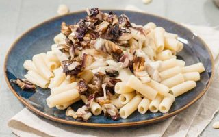 A close up of a ceramic blue plate full of a vegan pasta Alfredo sauce made with gluten-free noodles and a dairy-free cashew cream sauce and topped with sauteed radicchio.