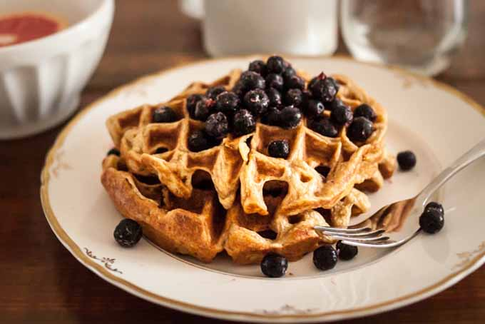 A close up of Crisp and Buttery Einkorn Waffles with Aronia Berries on a patterned porcelain plate on a dark wooden table.