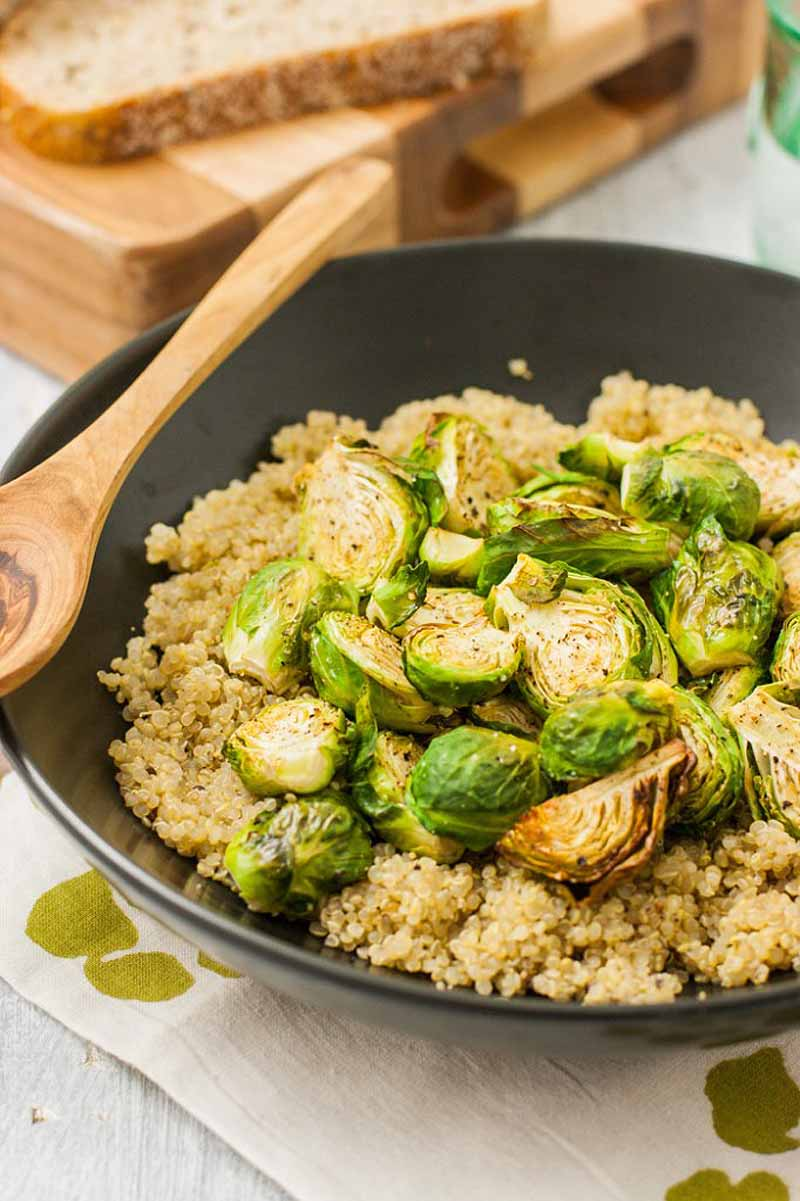 Oblique view of a black, nonstick skillet full of a roasted Brussels sprout and quinoa mixture. A wooden spoon sits on the lip of the pan.