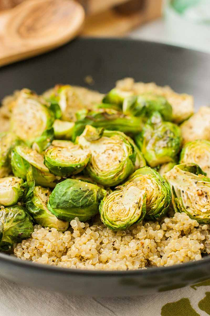Extreme closeup of a batch of roasted Brussels sprouts in a frying pan along with prepared quinoa.