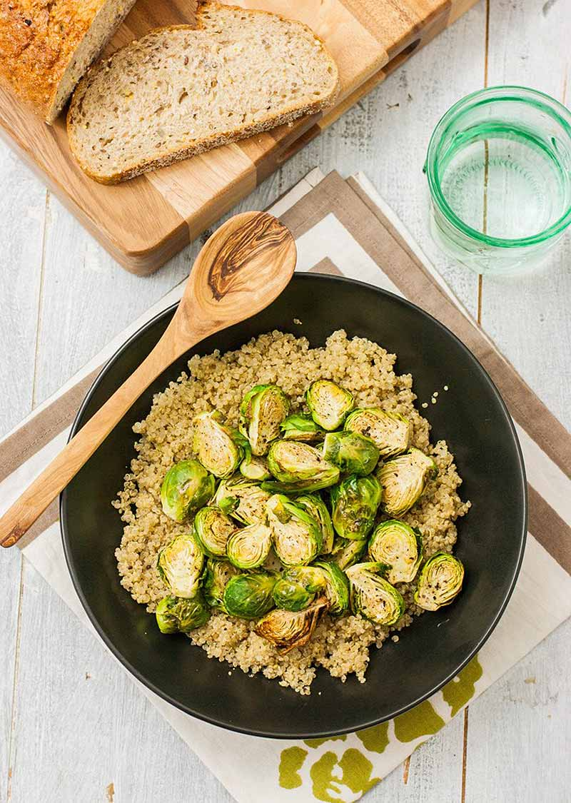 Top-down view of a frying pan full of roasted Brussels sprouts layered on bed of quinoa.