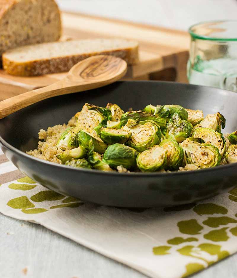 Oblique side view of a black frying pan full of roasted Brussels sprouts sitting on a white and green place mat. A wooden spoon is in the background.