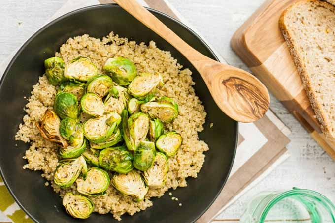 Top down view of a bed of quinoa in a black skillet with roasted Brussels sprouts layered on top. A wooden spoon sets on the lip of the pan and wooden cutting board with homemade bread sits to the left.