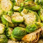 Extreme close up of a batch of roasted Brussels sprouts resting on a bed of prepared quinoa.