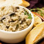 Close up of a white ceramic bowl full of vegan mushroom and herb risotto rice.