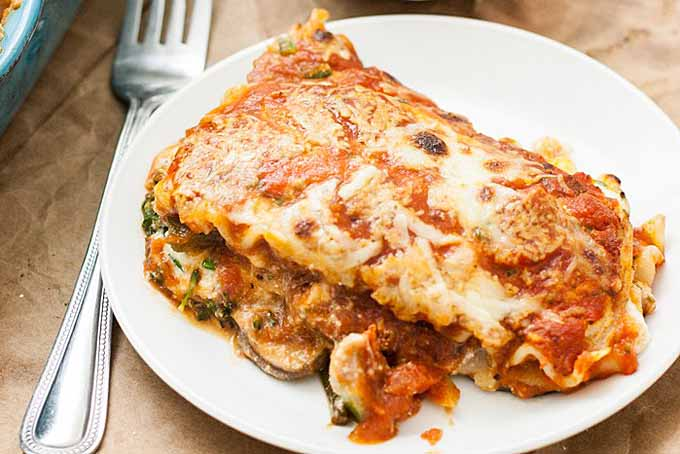 A slice of meatless lasagna mated with ricotta, pecorino romano, and mozzarella cheese along with mushrooms and broccoli. Sitting on a white ceramic plate.