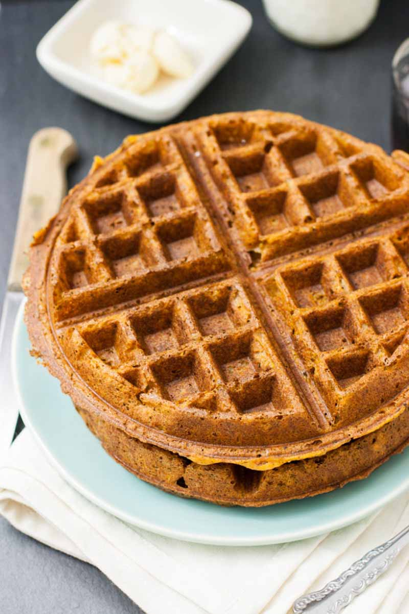 Close up and oblique view of a stack of two sweet potato waffles on a teal ceramic plate.