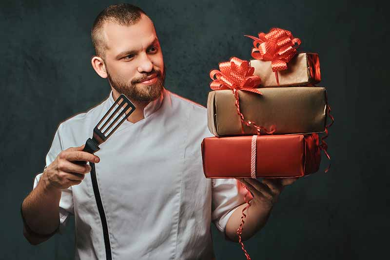 A man in a white chef's coat holds a metal spatula in this right hand, and a stack of presents wrapped in red and brown paper with red bows on top in the left, on a dark gray background.
