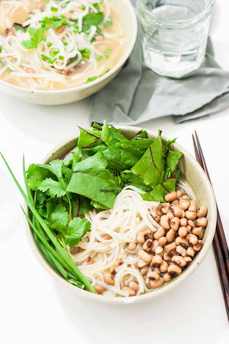 Top down, slightly oblique view of a bowl full of rice noodle, greens, and black eyed peas for New Years on a white background. Chop sticks sit to the right and a second bowl full at the top.