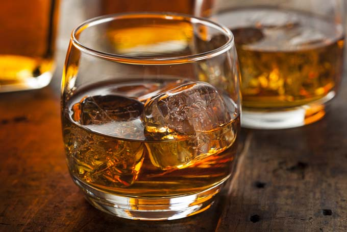 Two glasses of whiskey with ice, on a wood surface.