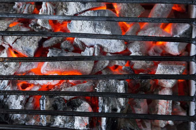 Spreading the charcoal evenly allows for direct heat grilling | Foodal.com