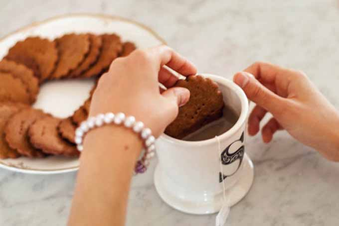The author dunking Einkorn Spelt Homemade graham crackers in a mug of tea