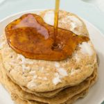 Horizontal image of freshly made pancakes with syrup.