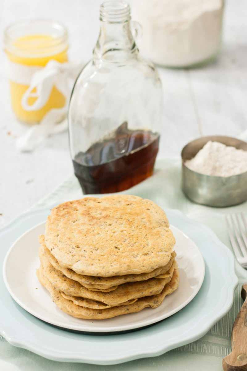 Vertical image of a stack of flapjacks with a bottle of syrup and flour in a cup.